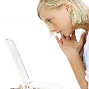 Young Woman Sitting Looking at Laptop Screen