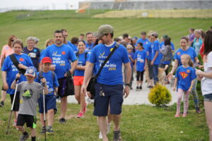 The picture shows people of a variety of ages walking on Fort Henry Hill at the annual Walk for Arthritis in 2018. They are wearing Walk for Arthritis shirts.