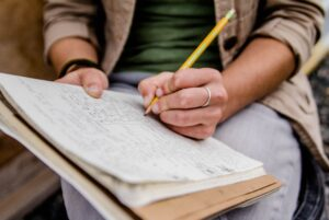 Person writing in a notebook or planner. Only hands and notebook are showing.