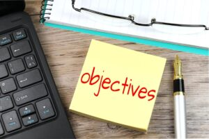 """Decorative image of laptop, pen and post-it note with message """"objective"""" in bold, red font"""